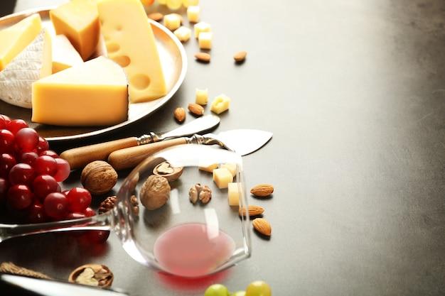 灰色のテーブルの上のおいしいチーズ、ブドウ、ナッツ、ワインの組成