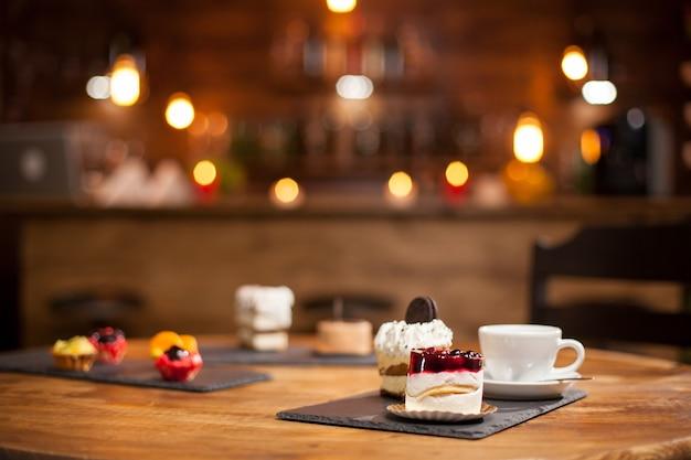 コーヒーショップの木製テーブルの上に、おいしい味のさまざまなケーキを組み合わせます。フルーツ入りの美味しいミニケーキ。上に美味しいビスケットが入ったケーキ。