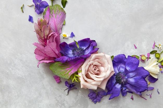 회색 배경 위에 표시되는 다른 꽃의 구성입니다. 꽃은 휴일이나 엽서를 디자인할 때 좋은 아이디어입니다.
