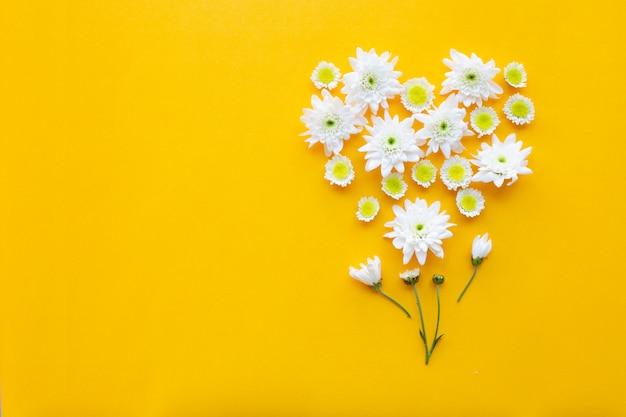 Композиция из цветов, хризантем на фоне желтой бумаги.
