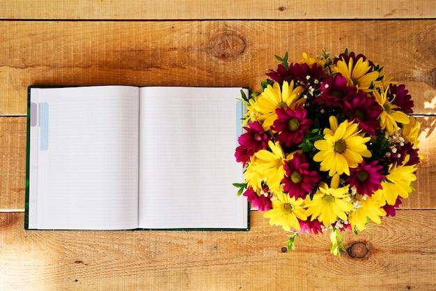 여름이나 봄철 아침에 나무 탁자에 있는 공책과 차 머그에 있는 꽃의 구성...