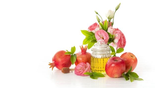 Композиция из цветов, гранатов, красных яблок и меда на белом фоне, традиционная еда еврейского нового года - рош ха-шана. свободное место для текста