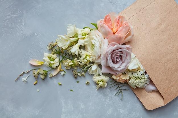 회색 배경에 봉투에 표현된 꽃의 구성. 발렌타인 데이에 남자의 여자를 위한 꽃다발. 다른 꽃과 장미입니다. 휴일 개념입니다.