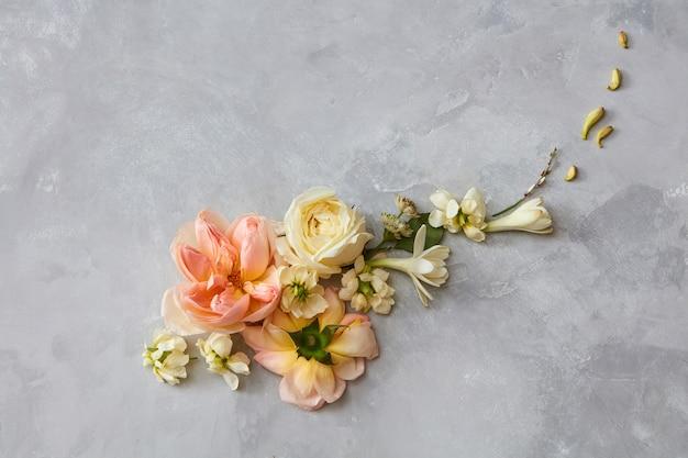 회색 배경에 표시되는 꽃의 구성입니다. 발렌타인 데이 개념입니다. 어떤 포스터를 디자인하기 위해 조직된 다른 꽃.