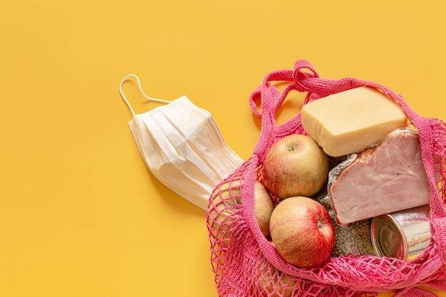 ストリングバッグ内の食品の組成をクローズアップ。食品の寄付または検疫中の食品配送の概念。