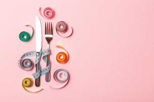 Состав вилки и ножа окруженный покрашенными balled измеряя лентами на розовой предпосылке.