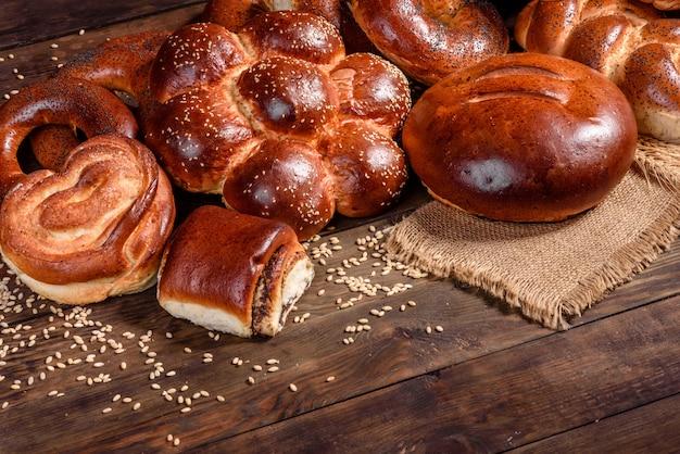Композиция из свежих запеченные сладкие булочки с маком и вареньем. сладкая выпечка выложена в виде композиции на деревянный стол