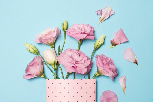 Композиция из свежих красивых розовых цветов в бумажной упаковке возле лепестков