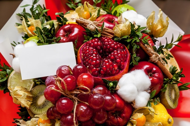 신선한 밝은 과일의 구성입니다. 석류, 포도, 사과, 키위, 오렌지, 레몬, 갈색 및 면으로 만든 과일 꽃다발