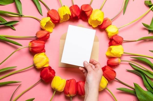新鮮な花、赤いチューリップの花束、封筒と紙テクスチャ背景の構成。国際女性の日、母の日挨拶コンセプト。