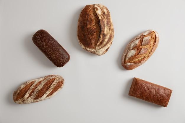 흰색 배경에 대해 반 원으로 배열하는 다른 종류의 신선한 유기농 빵의 구성. 빵집에서 구운 통 곡물 메밀 잡곡 호밀 빵. 소박한 천연 바이오 제품.
