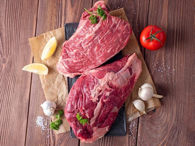 新鮮な牛肉、野菜、スパイス、木製の背景、紙の羊皮紙の構成。食べ物の写真。フラットレイ