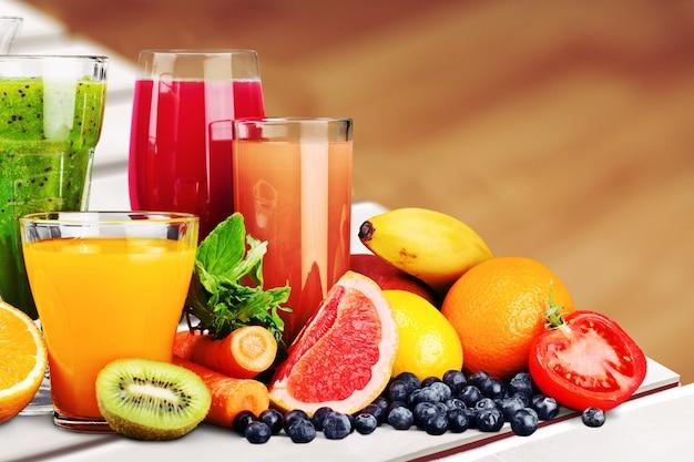 Композиция из фруктов и стаканов сока на размытом естественном фоне