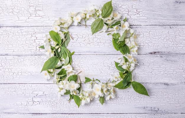 灰色の背景のテキストの空白のシートと緑の葉とジャスミンの花の構成
