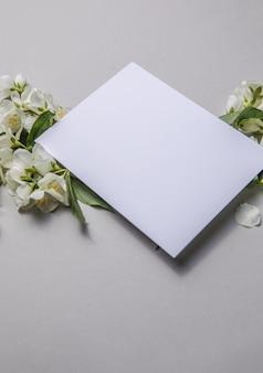녹색 잎과 회색 종이 배경에 텍스트에 대 한 빈 시트와 재스민의 꽃의 구성. 엽서에 대 한 자연 레이아웃입니다. 플랫 레이