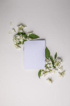 緑の葉とジャスミンの花の構成と灰色のテキストの空白のシート