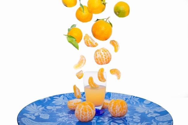 Композиция из кусочков лимона и апельсина, падающих в стакан для сока средиземноморская диета