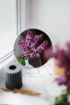 Композиция из сиреневых цветов и зеркала. минималистичный декор с copyspace