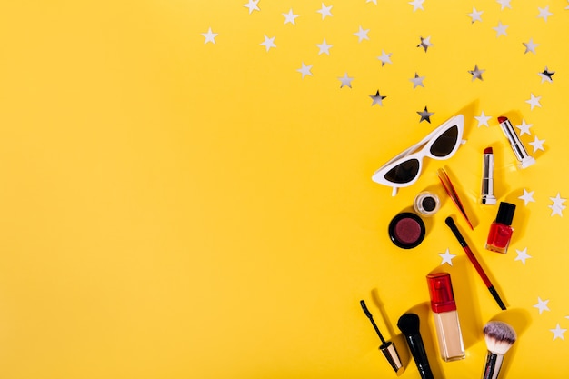 Композиция из кистей для макияжа, тональной основы, подводки для глаз, губной помады, туши и стильных солнцезащитных очков на оранжевой стене с серебряными звездами