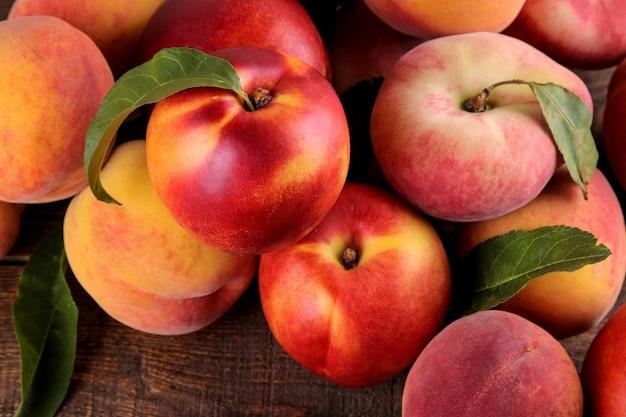 Композиция из многих сортов персика на коричневом деревянном столе. фрукты.