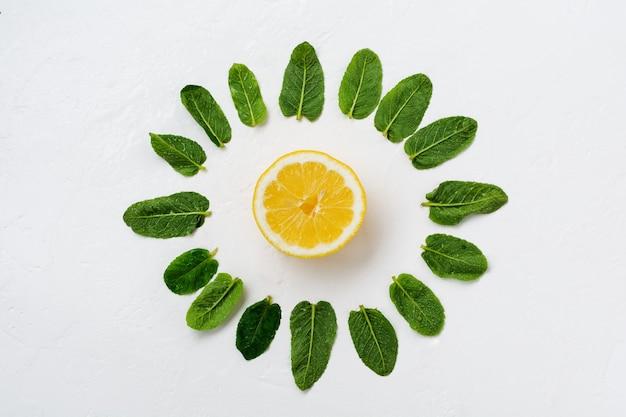 白い古いコンクリートの背景にミントの葉、レモン、サトウキビの砂糖の断片の構成。