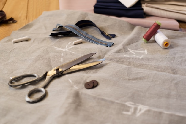 Сочетание иглы и нитки с другими швейными инструментами. катушка с нитками, ножницы, пуговицы, швейные принадлежности. закройте ножницы, пуговицы, нить и наперсток на ткани.