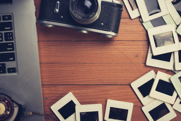 Композиция старого фотоаппарата, ноутбука и слайдов