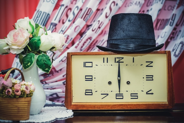 Композиция из старых деревянных часов и черной шляпы