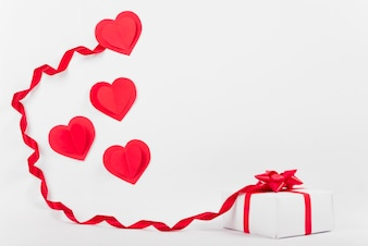 Composition of ornament paper hearts near present box and ribbon
