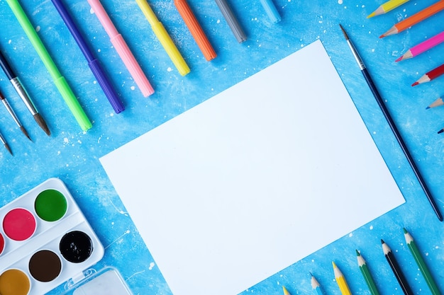도장기구의 구성. 연필, 마커, 브러쉬, 페인트 및 종이. 파란색 배경