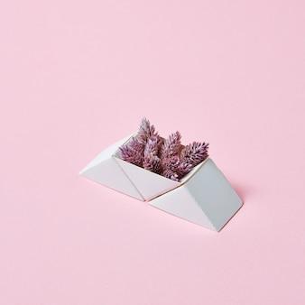 コピースペースとピンクの背景に円錐形の紙の三角形のボックスの構成。はがきのレイアウト