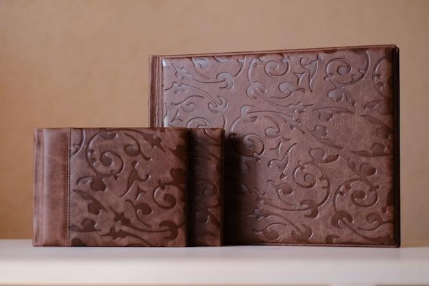 Композиция из фотокниг из натуральной коричневой кожи разных размеров. фрагмент переплета фотокниги