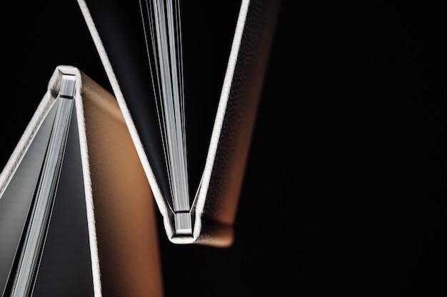 Композиция из фотокниг из натуральной белой кожи разных размеров. белая бумага на темном фоне.