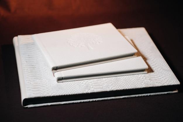 Композиция из фотокниг из натуральной белой кожи разных размеров.