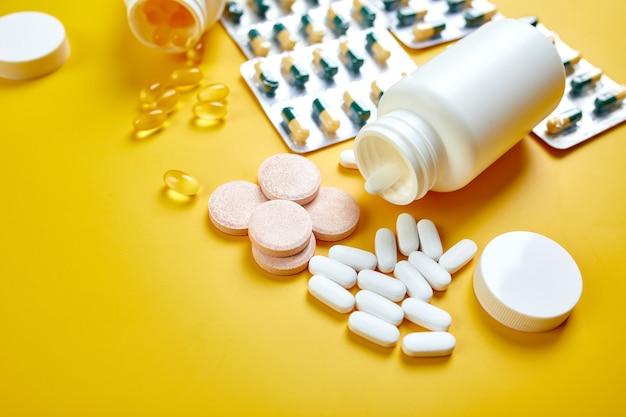 Состав таблеток, рыбьего жира, витаминов на желтой поверхности