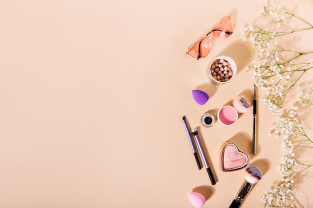 핑크 블러쉬, 메이크업 브러쉬 및 하트 모양의 안경의 구성은 귀여운 꽃 사이에 놓여 있습니다.