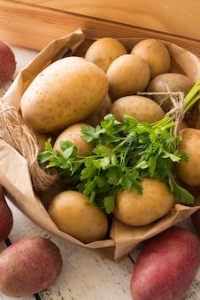 Композиция из сырого картофеля в бумажном пакете на деревянном фоне
