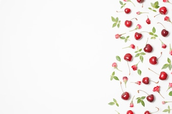 Composition of red blooms, cherries and green leaves