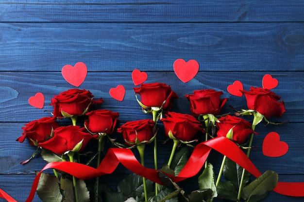 Композиция из красных роз и сердечек на синем деревянном фоне, день святого валентина. место для текста.