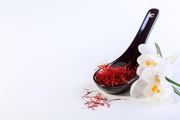 セラミックスプーンと白い背景の上のクロッカスの花の赤いサフランのスレッドの構成