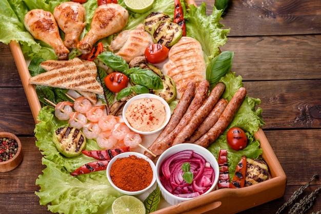 그릴에 준비된 소시지, 닭고기, 돼지 고기 및 새우와 향신료와 허브를 곁들인 그릴에 준비된 야채 구성. 불에 요리