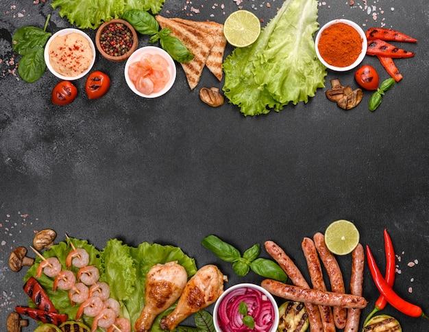 グリルで調理したソーセージ、チキン、ポーク、エビ、スパイスとハーブを使ったグリルで調理した野菜の組成。火で調理