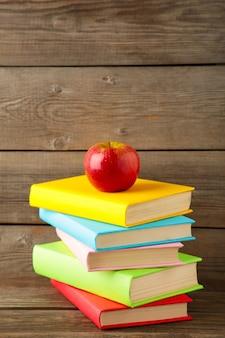 Композиция из школьных учебников и яблоко на сером фоне деревянных