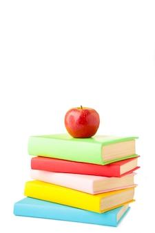 Композиция из школьных учебников и яблок на белой стене