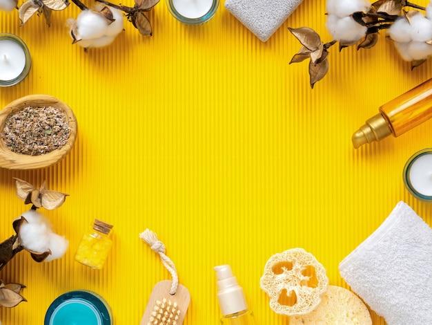 セルフケアのものの構成。黄色の背景にスポンジ、ブラシ、クリーム、ボトル、キャンドル