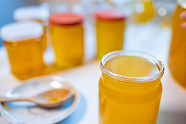 明るい晴れた日に大きな白いテーブルの上に黄色い甘い蜂蜜と大きな木のスプーンで小さな受け皿といくつかのガラスの透明な瓶の構成