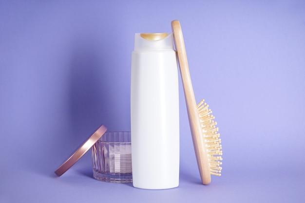 Состав бутылки шампуня и деревянной расчески на фиолетовом фоне.