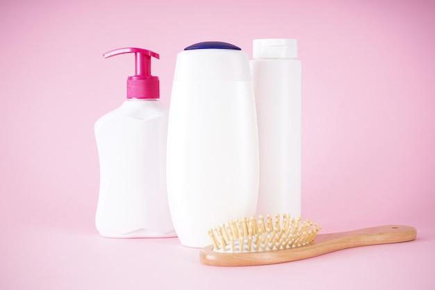 Состав флаконов шампуня, дозатора мыла и деревянной расчески на розовом фоне.