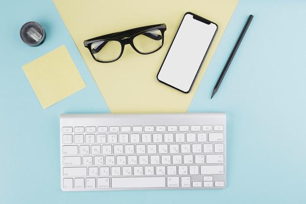 Композиция смартфона, клавиатуры, очков и карандаша
