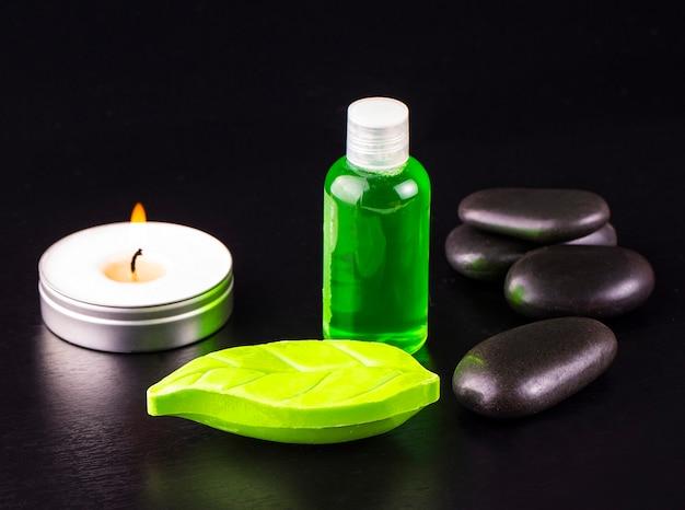나무 테이블에 스파 트리트먼트의 구성입니다. 비누, 촛불, 블랙 테이블에 오일과 스파 돌의 병.